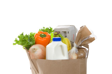Brown eco friendly grocery bag with bottle of milk, carton of eggs, bag of bread, bananas, lettuce, bell pepper and onion, isolated on white. Healthy shopping.