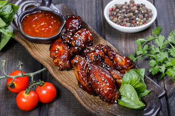 Barbecue chicken wings with bbq sauce on plate on wooden background. Hot Meat Dishes