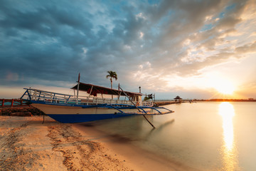 Boat on the beach shore of a white sand beach in the Philippines