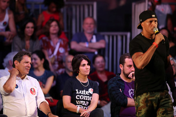 Presidential candidate Fernando Haddad (L) and his vice-president candidate Manuela D'avila (C) observe as Brazilian singer Mano Brown talks during a rally in Rio de Janeiro