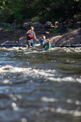 Father and daughter paddle a canoe on whitewater in the Canadian wilderness