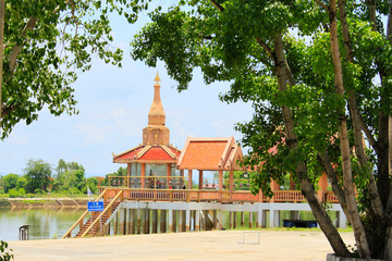 Long shot of the main temple with steps leading to lake framed by trees Buang Sam Phan, Phetchabun, Thailand