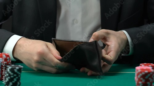 Male looking in his empty wallet, lost all money, gambling