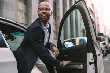 Young businessman getting down from car