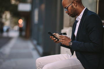 Businessman relaxing outdoors with phone and coffee