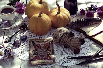 Still life with voodoo doll, the Devil tarot card, cup of tea and pumpkins. Mystic background with ritual objects, occult, fortune telling and halloween concept