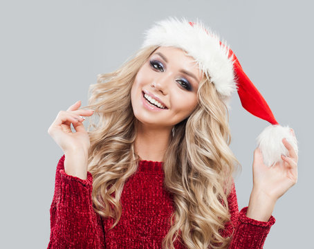 Young beautiful blonde woman in knited sweater and christmas hat smiling over white background.