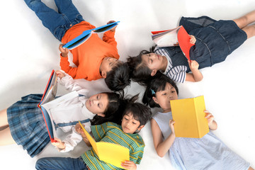 Kids reading book laying on the white floor ,head to head, in a circle group, preschool library,Kindergarten school education concept