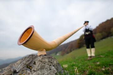 Alpine horn. A man plays in an alpine valley