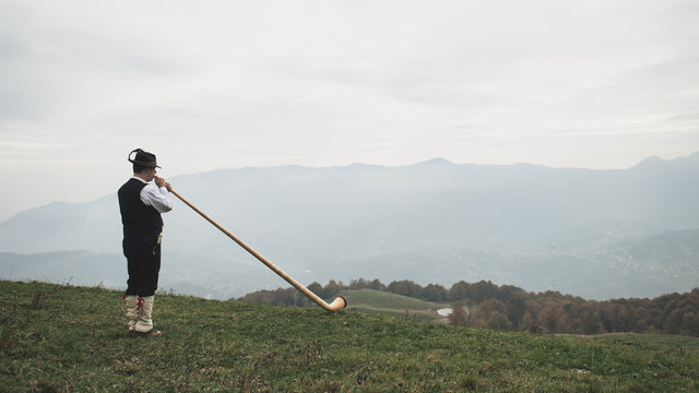 Playing the alpine horn in front of a valley in the Alps