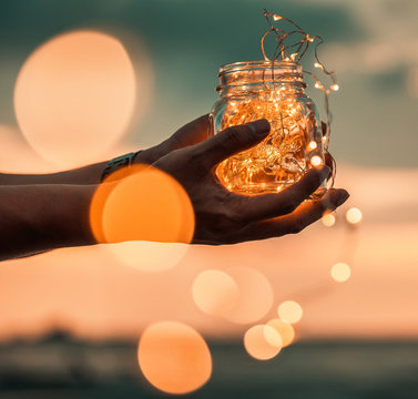 man hold Transparent jar with lights from led on beach in the sunset . Give a Gift. Romantic Hipster Concept.