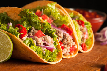 Photo of Mexican tacos with ground beef, onion, tomatoes, chili, red sauce, lettuce and lime on wooden background. Spicy and fast food concept.