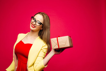 Studio portrait of happy beautiful girl with red lips and cat-eye glasses wearing festive elegant red dress and yellow jacket holding wrapped gift box with red ribbon. Isolated on red background.