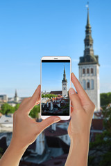 A tourist is taking a photo of the old city of Tallinn from above on a mobile phone