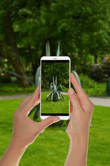 A tourist is taking a photo of a big aloe in the Bernardine Park in Vilnius, Lithuania on a mobile phone
