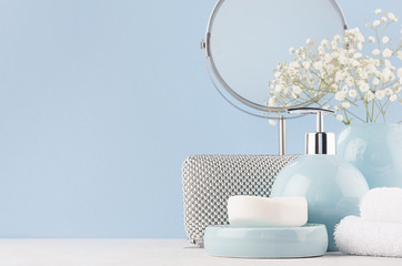 Products for body and skin care in light blue ceramic bowls, silver cosmetic bag, circle mirror and white flowers on wood table and pastel blue wall.