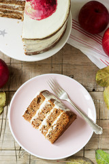 Apple cake with curd cream, decorated with painted apple on the background of autumn composition. Rustic style.