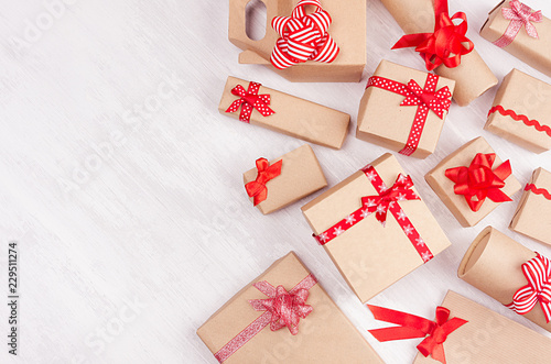 new year celebration background homemade craft paper gifts with red ribbons and bows on white