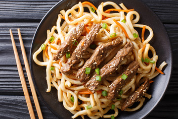 Portion of beef teriyaki with udon noodles, carrots and green onions close-up on a plate. horizontal top view