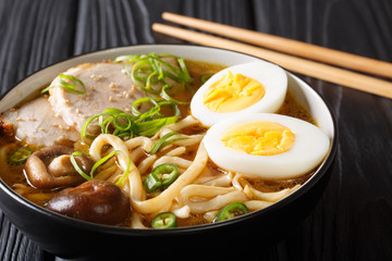 Traditional Japanese udon noodle soup with pork, boiled eggs, mushrooms and green onions closeup in a bowl. horizontal