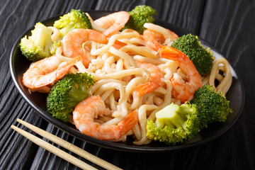 Asian style udon noodles with shrimp, broccoli and soy sauce close-up on a plate. horizontal