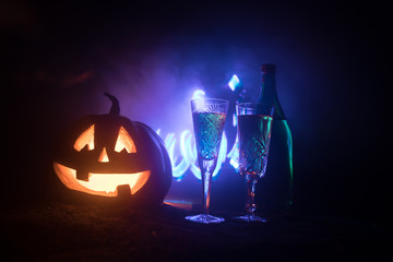 Two glasses of wine and bottle with Halloween - old jack-o-lantern on dark toned foggy background. Scary Halloween pumpkin