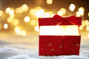 Weihnachtsgeschenk im Schnee mit Bokeh Hintergrund