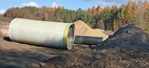 Large sewer pipes  and  pile of sand  in  a autumn forest  construction site