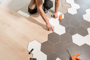 Male worker installing new wooden laminate flooring. The combination of wood panels of laminate and ceramic tiles in the form of honeycomb. Kitchen renovation.
