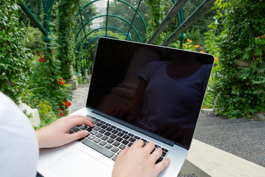 Laptop laying on woman knees in park mockup