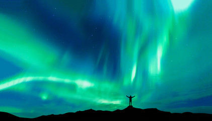 Tuinposter Noorderlicht Aurora borealis with silhouette standing man on the mountain.Freedom traveller journey concept