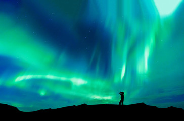 Aurora borealis with silhouette standing man on the mountain.Freedom traveller journey concept