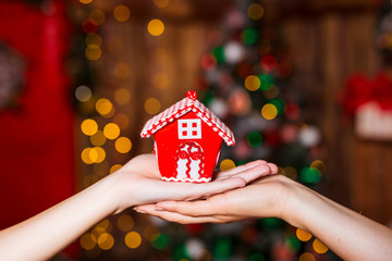 Human hands holding decorative red house against blurred background. Christmas and home comfort concept.