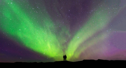 Tuinposter Noorderlicht Aurora borealis with silhouette love romantic couple on the mountain.Honeymoon travel concept