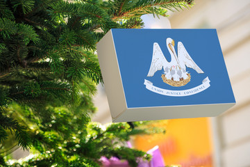 Louisiana state flag printed on a Christmas gift box. Printed present box decorations on a Xmas tree branch on a street. Christmas shopping in United States, local market sale and deals concept.