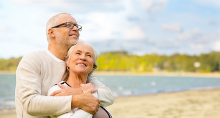old age, retirement and people concept - happy senior couple hugging over beach background