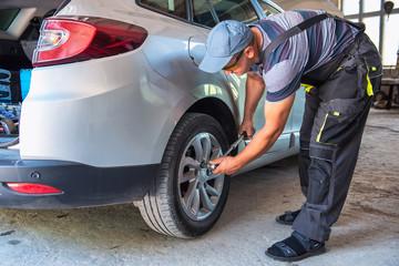 Car service worker diagnoses car breakdown.