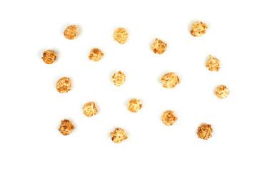 Few pieces caramel popcorn on white background.