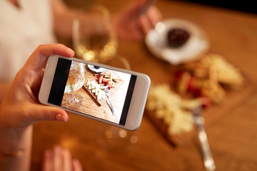people, technology and lifestyle concept - hand picturing food by smartphone at wine bar