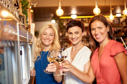 people, alcohol tasting and lifestyle concept - happy women drinking wine and toasting at bar or restaurant
