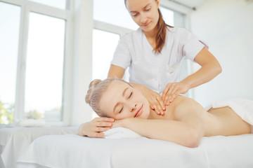 Body massage. Beautiful blond woman in spa salon doing body massage.