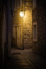Old street at night illuminated by vintage streetlight.