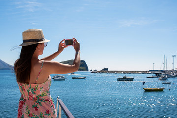 Young beautiful brunette girl in hat making selfie using phone while standing on the luxury yacht