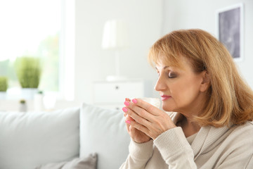 Beautiful mature woman drinking coffee at home
