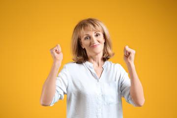 Portrait of happy mature woman on color background