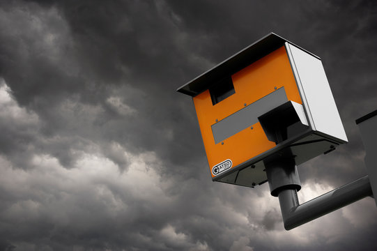 YELLOW GATSO ROAD SAFETY SPEED CAMERA AGAINST STORMY GREY SKY