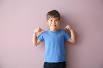 Cute little boy pointing at his t-shirt on color background