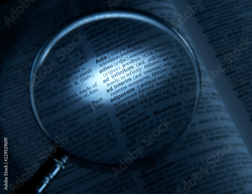 MAGNIFYING GLASS ON DICTIONARY PAGE SHOWING DEFINITION OF THE WORD