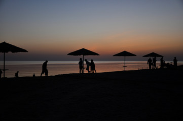 silhouettes of people at sunset on the background of the sea