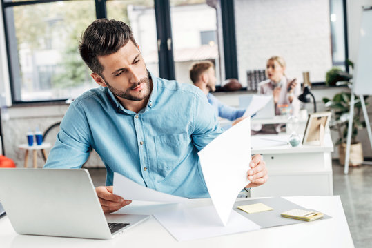 concentrated young businessman working with papers and laptop in office